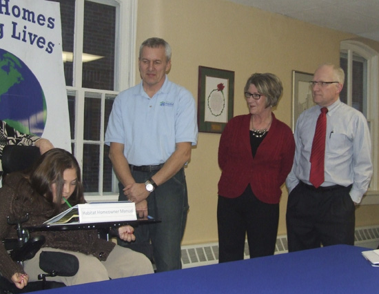 Dan Von der Embse and Randy and Sue Basinger (r) family advocates, look on as Jodi Young signs to be a partner family with Putnam County Habitat for Humanity. (Putnam Sentinel/Nancy Kline)