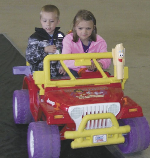 Owen Siebeneck rides as a passenger while Kendall Krouse drives the vehicle during Safety City on Wednesday. (Putnam Sentinel/Nancy Kline)
