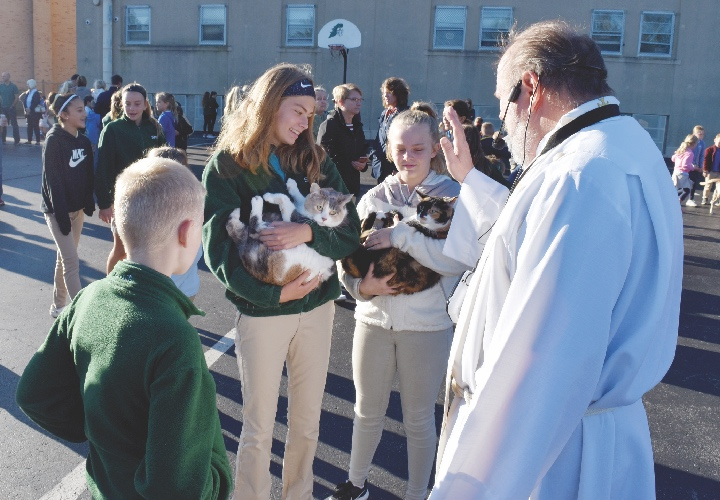 Ashley (right) and Morgan Inkrott hold Maggie and Cali for blessing by Father Josefiak - Putnam Sentinel