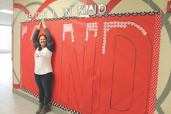 "Columbus Grove School Nurse, Mrs. Katie Zimmerly poses as the ""I"" in ""Kind"" in the craft mural outside of her station. Students and staff who donate an item to the Caring Closet write their name in a heart and place it onto the mural before a photo of their own is taken - Putnam Sentinel"